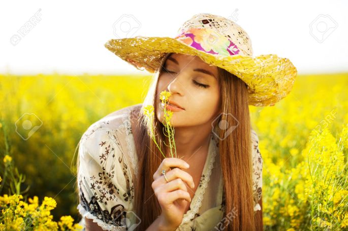25750241-happy-girl-in-a-hat-enjoying-the-smell-of-the-flower-stock-photo