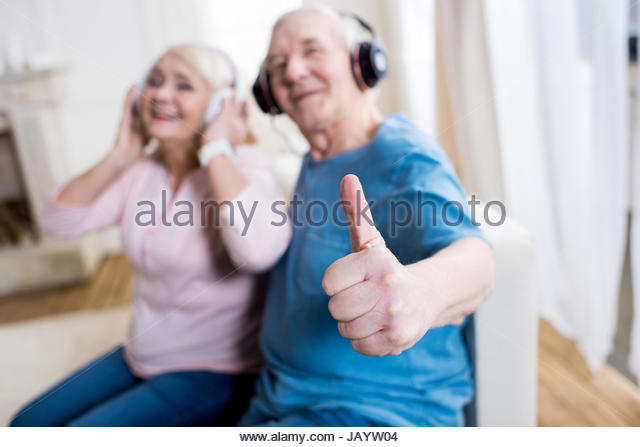 happy-senior-couple-in-headphones-sitting-together-and-showing-thumb-jayw04